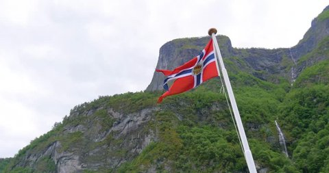 A 4K shot of a Norwegian flag blowing in the wind on a fjord cruise.
