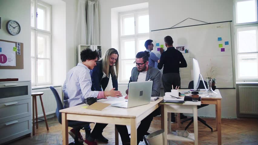 Group of young businesspeople with laptop working together in a modern office. | Shutterstock HD Video #1026803276