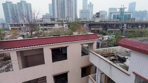 GUANGZHOU, CHINA. Cluster of high-density, low-cost housing with modern high rises in the background. Demolished and vacated buildings in Xiancun village.