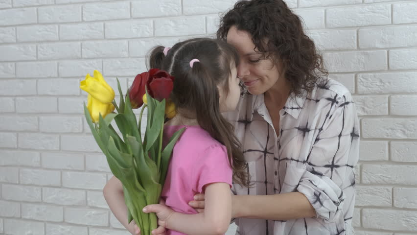 The child congratulates the mother. Daughter gives mother flowers.