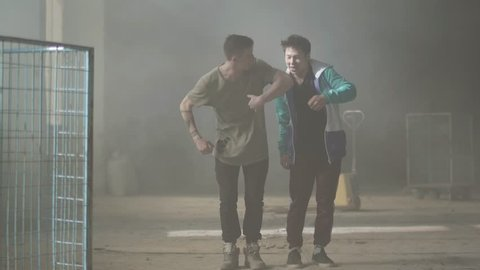 Two young men dancing in the dark and dusty room of abandoned building. The guys making dance moves and poses. Friends practicing in break-dance. Hip hop culture. Rehearsal. Contemporary.
