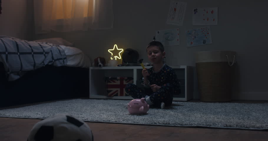 Cute little kid boy wearing pajama prepares to break his piggy bank with savings, bedroom interior evening shot. 4K UHD RAW FOOTAGE | Shutterstock HD Video #1026833006