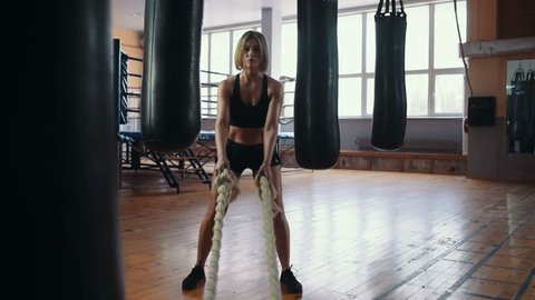 Young athletic girl who is engaged in boxing, doing strength exercises using ropes in the gym.