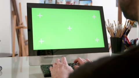 Man types continuously in front of a green screen. Artists workshop in the background. Designer working in his studio.