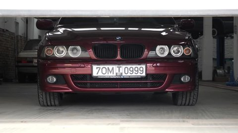 MINSK, BELARUS - March 20, 2019: Car service station gate opens up and reveals shiny clean 2002 BMW E39. Car service concept.
