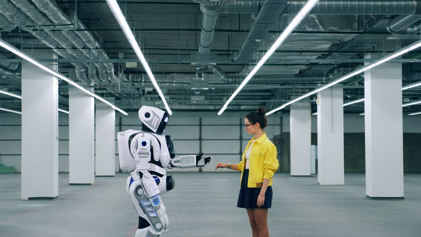Girl and droid touch hands while meeting in a room. | Shutterstock HD Video #1026880466