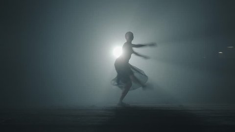 Diligent young graceful ballerina dancing elements of classical ballet in the dark with light and smoke on the background. Beautiful young ballerina in darkness. Ballet practice in studio.