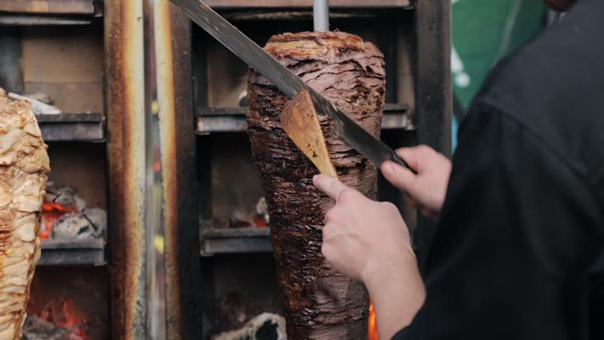 Close up tilt down shot of cook cuts juicy beef to make shawarma, gyros, doner kebab. Cooking beef meat on a skewer during street food market   Shutterstock HD Video #1026906566