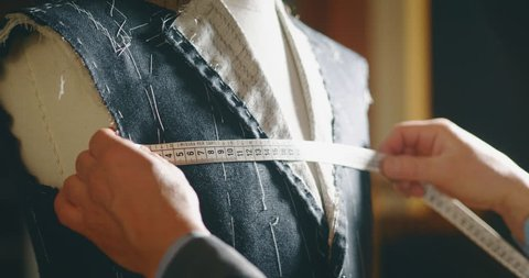 Slow motion of tailor taking a measures  for a new handmade great quality suit  in atelier.