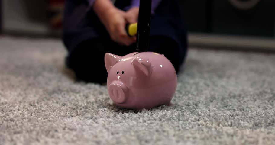 CU Cute little child girl prepares to break her piggy bank with savings, bedroom interior evening shot. 4K UHD RAW FOOTAGE | Shutterstock HD Video #1026914276