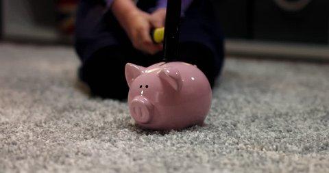 CU Cute little child girl prepares to break her piggy bank with savings, bedroom interior evening shot. 4K UHD RAW FOOTAGE