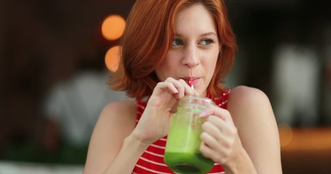 Pretty girl drinking green juice. Redhair young woman holding detox drink smiling and laughing