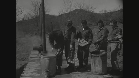 CIRCA 1956 - American soldiers stationed in Korea enter the mess hall, while others come out and empty their trays.