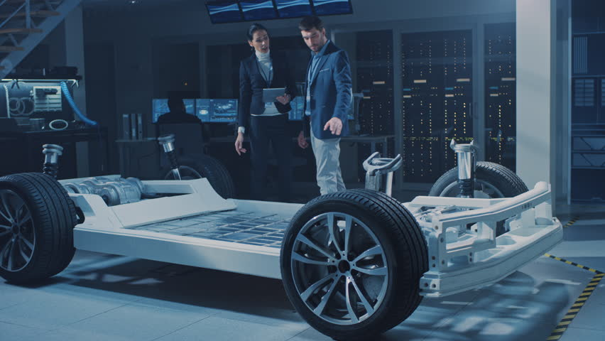 Female Chief Engineer Uses Tablet Computer, Introduces Autonomous Electric Car Concept to Important Investor, Describing Efficiency of Hybrid Engine. Vehicle Chassis Has Wheels, Engine and Battery