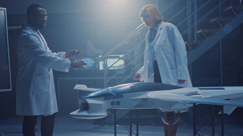 Two Aerospace Engineers Work On Unmanned Aerial Vehicle / Drone Prototype. Aviation Scientists in White Coat, Use Blueprint. Laboratory with Commercial Aerial Surveillance Aircraft