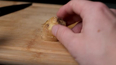 Using a spoon to scrap the skin from a ginger tuber.