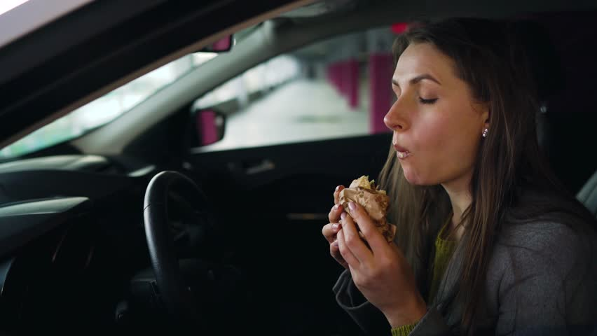 Woman eating sandwich sitting in the car on the parking. Concept of a modern busy life | Shutterstock HD Video #1027022366