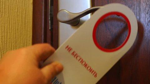 KRASNODAR, RUSSIA - CIRCA 2019: Russian 4-star hotel Intourist room door sign Do Not Disturb. Guest putting door hanger on handle.
