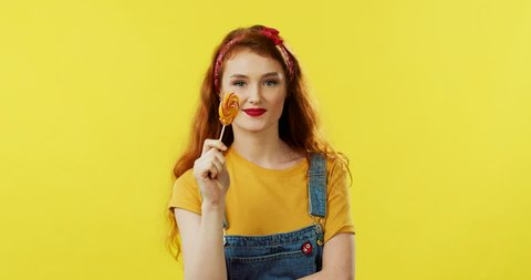 Portrait of the joyful Caucasian young red-haired girl licking lollipop and laughing a lot to the camera on the yellow background.