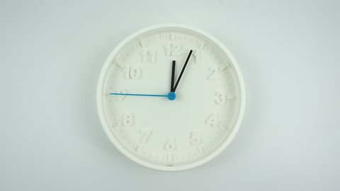 Eat lunch Twelve o'clock Close up White clock face beginning of time 12.05 am, White wall clock Blue second hand minute Walk slowly, Time concept.