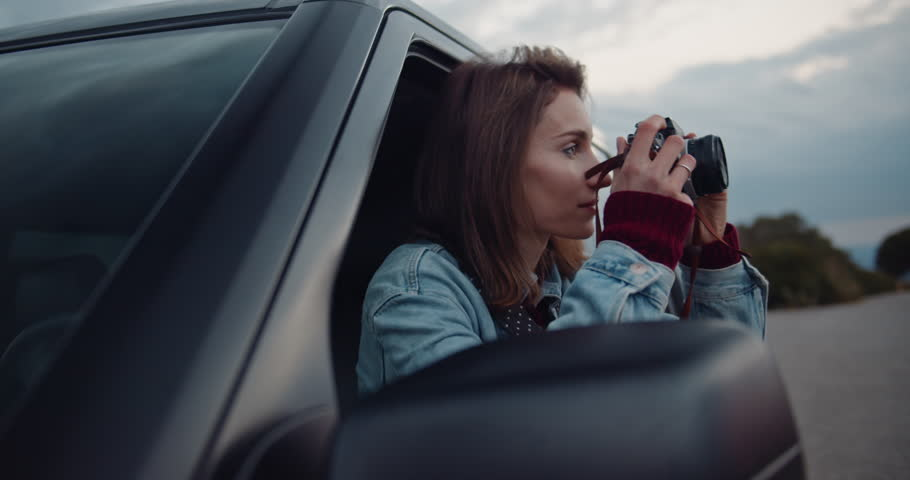 Shot of young woman taking photos while sitting in a car. Attractive female in hipster look capturing a perfect road trip moment on retro film camera, Shot on cine camera, slow motion 4K | Shutterstock HD Video #1027149836