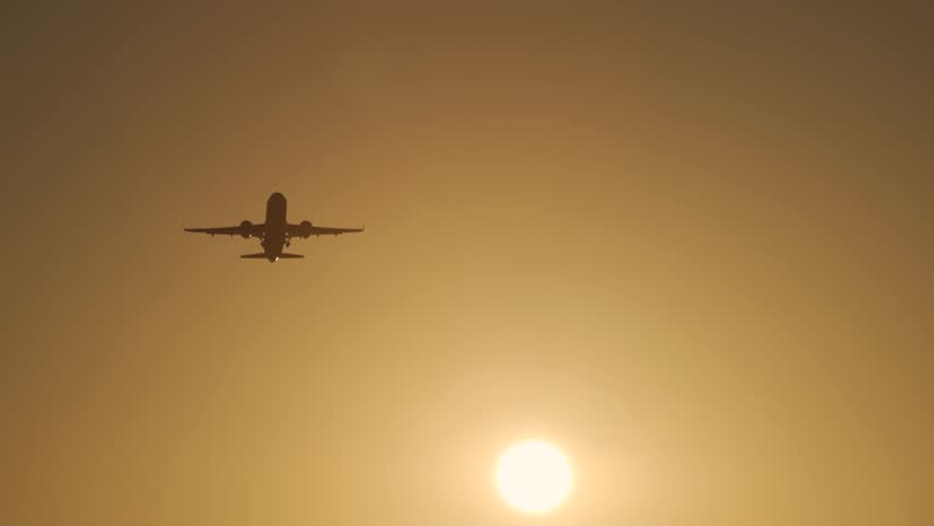 Airplane takes off at dawn from the runway in the background of the sun at sunset in the rays of yellow light. Aircraft cleans the chassis gaining height and speed.   Shutterstock HD Video #1027152086