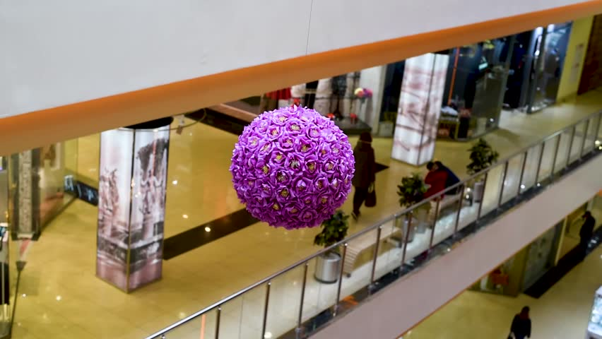 A ball of artificial pink and lilac flowers for beauty , design or decor swings on a fixed rope creating a mood. Decorates a shop space or office room Decor of artificial flowers in the shape of a bal