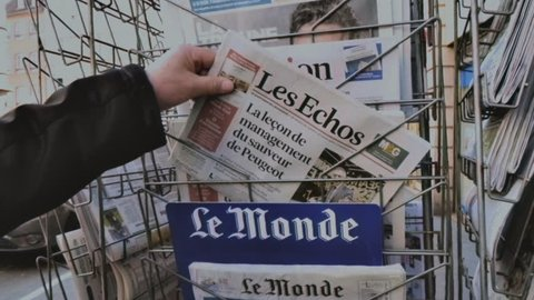 Paris, france - 29 mar 2019: newspaper stand kiosk selling press with  senior male hand buying latest economical les echo featuring news about  peugeot car maker on front cover vhs vintage tape