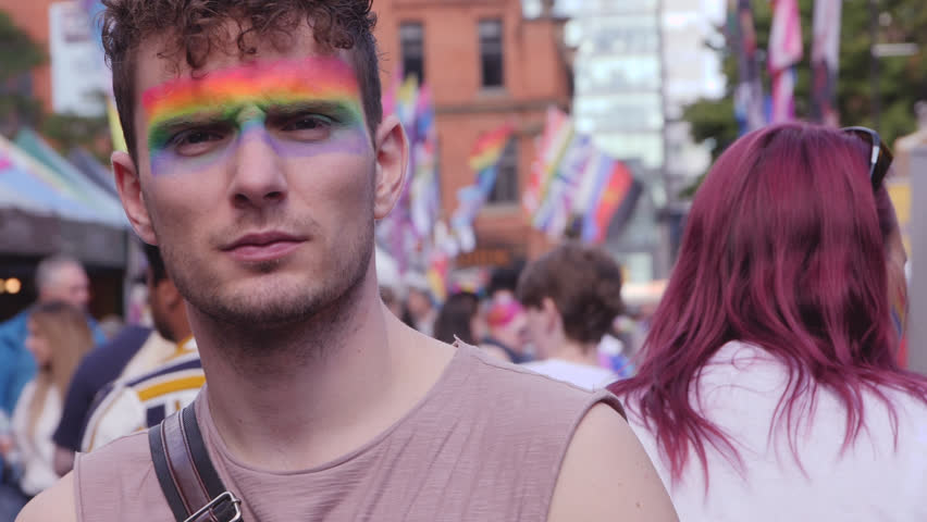 Guy with serious eyes and facepaint on at LGBTQ Pride, Lesbian, Gay, Bisexual, Transgendered, Queer, Parade with rainbow flags and slow motion