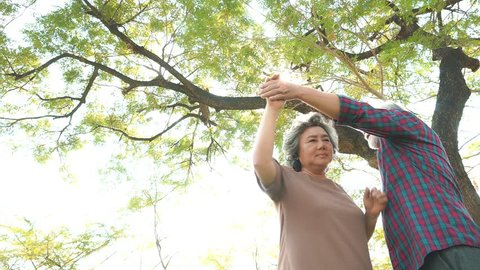 Old woman of wife dancing with her husband or old man at park under tree. Grandmother and grandfather feel happiness in the wonderful moment time with smiley faces. Old couple is romantic couple