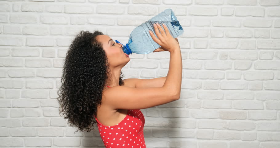 Young people, health and wellness. Portrait of happy african american woman drinking mineral water from plastic bottle. Thirsty black girl with drink container in summer. Person and healthy lifestyle
