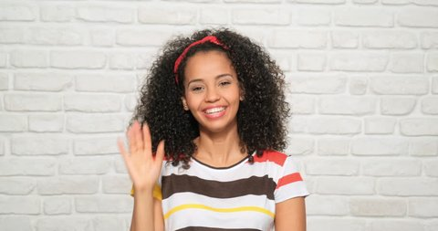 Young people, feelings and emotions. Portrait of happy african american woman saluting. Black girl waving hands for bye-bye, ciao. Cheerful latina person smiling for joy, laughing, saying good-bye