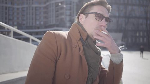 Portrait of handsome man in brown coat standing in the city street wearing sunglasses. The guy smoking cigarette. Leisure of the attractive guy. Cityscape in the background. Slow motion