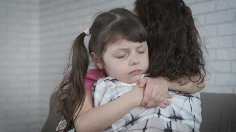 Depressed child hugs mother.