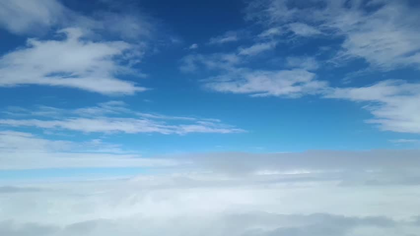 View from the window of the plane at the white clouds in the sky | Shutterstock HD Video #1027309826