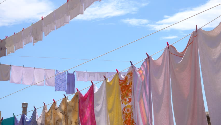 CLOSE UP: Warm summer air dries the freshly washed laundry hung out to dry on a sunny day in Greece. Colorful sheets, clothing and towels hang from the clotheslines under the clear blue summer sky.
