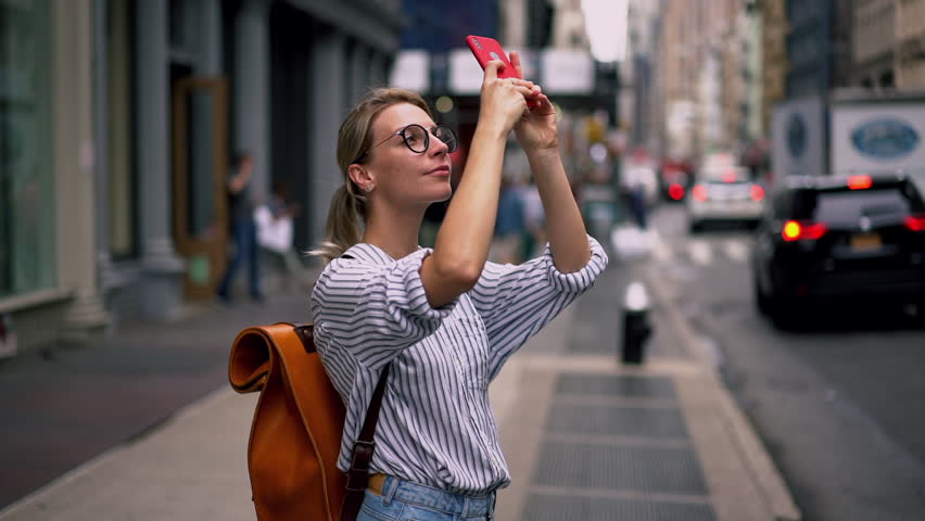 Millennial hipster girl tourist in casual outfit photographing buildings architecture and in New York using camera and application on modern cellular phone, slow motion effect. Female wanderlust  | Shutterstock HD Video #1027369256