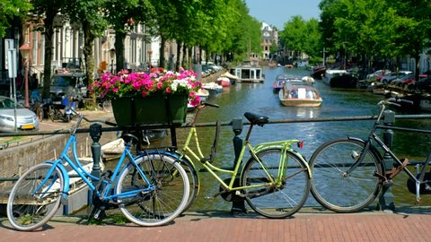 Typical Amsterdam view - Amsterdam canal with boats and bicycles on a bridge. Amsterdam, Netherlands