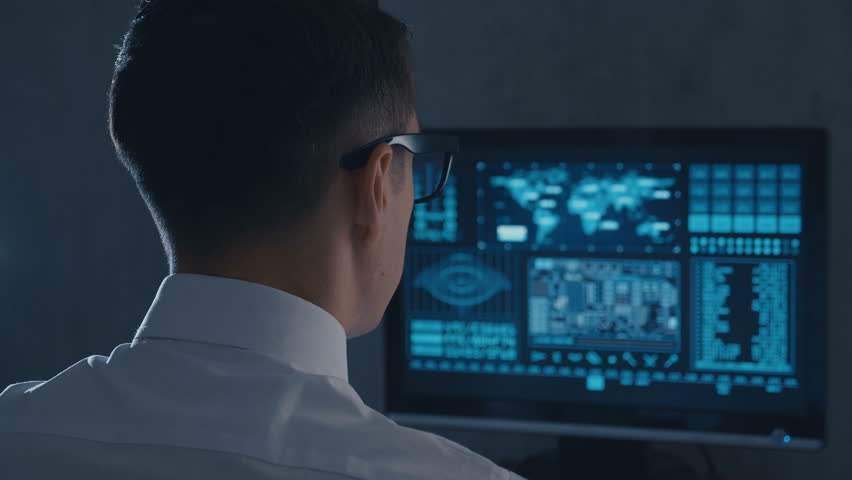 Back view of man programmer in glasses and white shirt working at computer in the data center | Shutterstock HD Video #1027423106