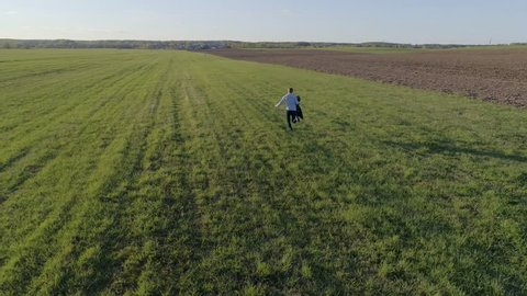 A man/guy dressed in jeans and a shirt with a jacket in his hand runs across the open field to meet a girl in a blue dress on a Sunny spring/summer day, aerial photography,