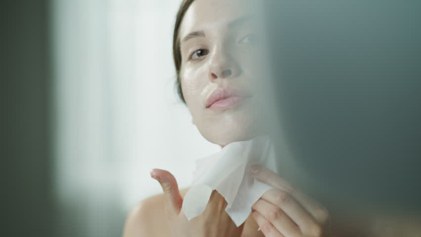 Close up of woman rubbing moisturizer on face with washcloth in mirror / Cedar Hills, Utah, United States | Shutterstock HD Video #1027452476
