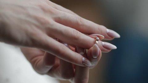 Elegant blonde bride wear beautiful engagement ring. Bride wears wedding ring at the finger at wedding morning