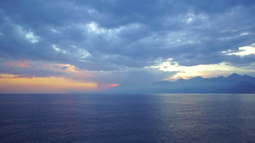 Aerial top view of peaceful calm dark blue sea water surface, cloudy sunset or sunrise sky and silhouettes of mountains. Real time 4k video footage. | Shutterstock HD Video #1027455026