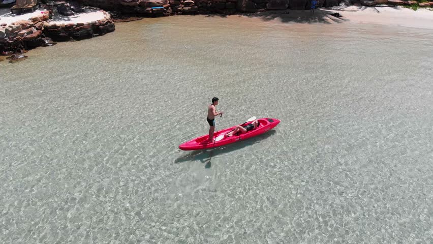 Young Asian couple Kayaking in the ocean on vacation, Drone shot footage.