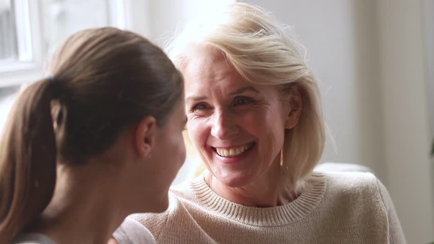 Happy old senior mother talking to adult daughter sharing news gossiping telling funny story, mature woman and young friend enjoy fun conversation laughing in different age generation friendship
