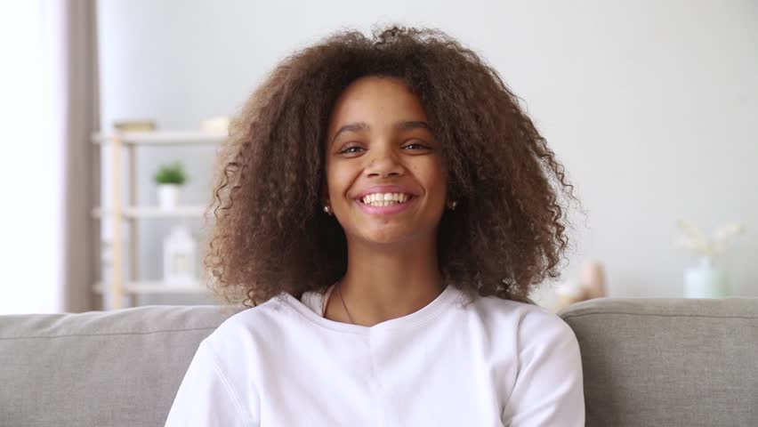 Happy african american teenage girl talking to camera make video call shooting blog for online channel, pretty black teen blogger vlogger speaking looking at webcam having fun laughing