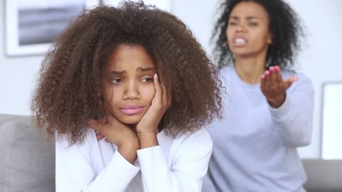 Sad teen african american girl upset by strict mum arguing scolding daughter, stressed stubborn teenager turned back ignoring angry black mother lecturing difficult kid, parent and children conflicts
