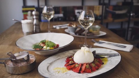 Burrata cheese stands on a wooden table in a cafe. In the restaurant, food and wine are on the table. Several ready-made dishes stand on a wooden table.