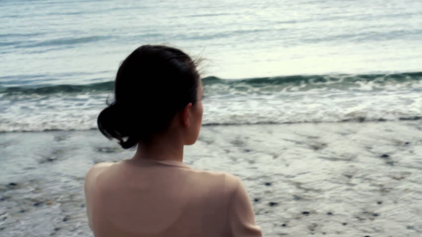 Young woman thoughtfully looking out to sea, camera stabilizer shot