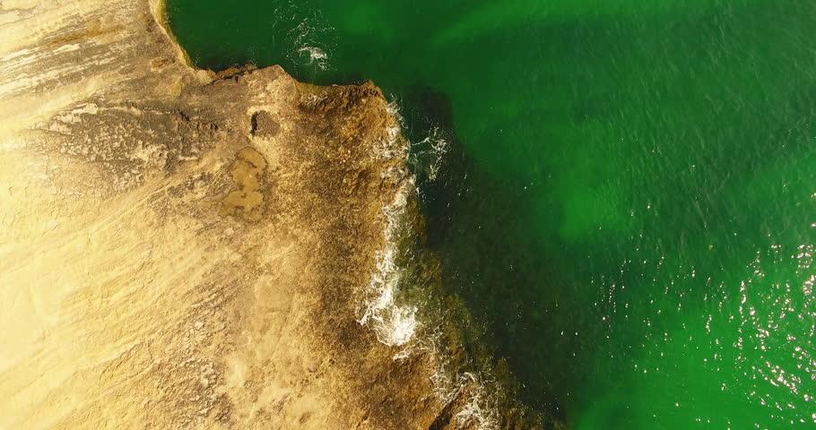 A bird eye view aerial shot of ocean rock island and green water An aerial bird eye view of persian gulf coast line and rock beach green water natural sun light no people | Shutterstock HD Video #1027544756